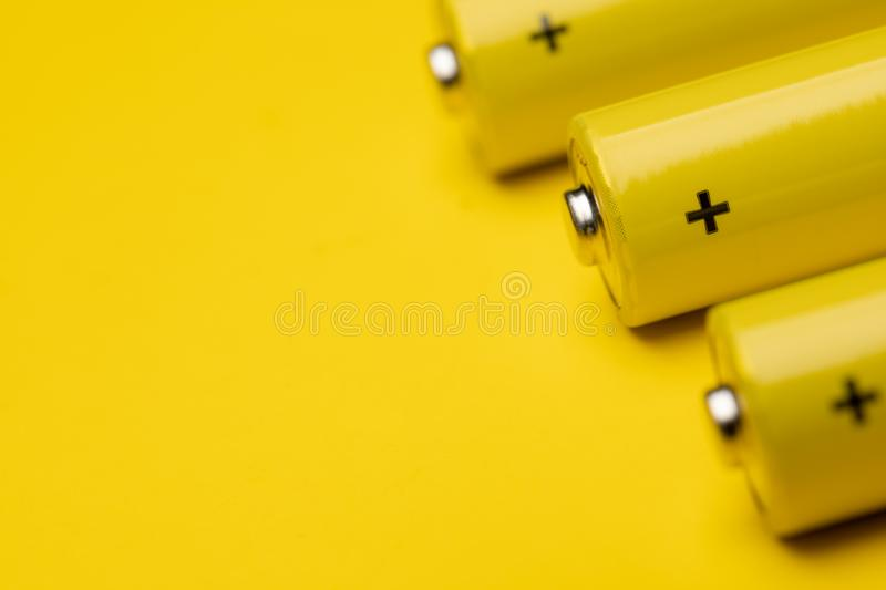 Yellow alkaline batteries colorful background. Close up shot of yellow AAA alkaline or rechargeable NiMH batteries or on yellow background, shallow focus stock photos