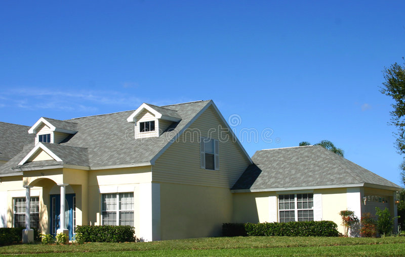 Yellow American dream home with garage. Yellow american dream home against perfect blue sky and garage royalty free stock images