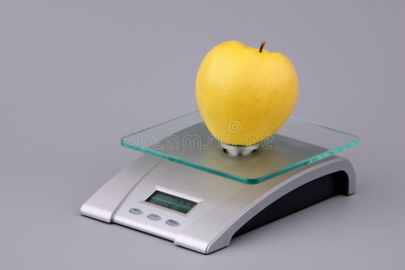 Yellow apple on scales. Yellow apple and scales on a grey background stock images