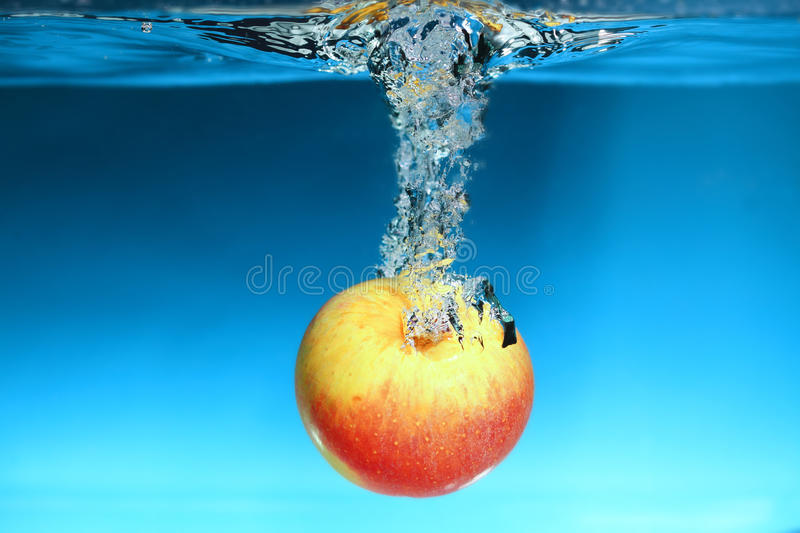 Yellow apple in the water splash over blue royalty free stock photography