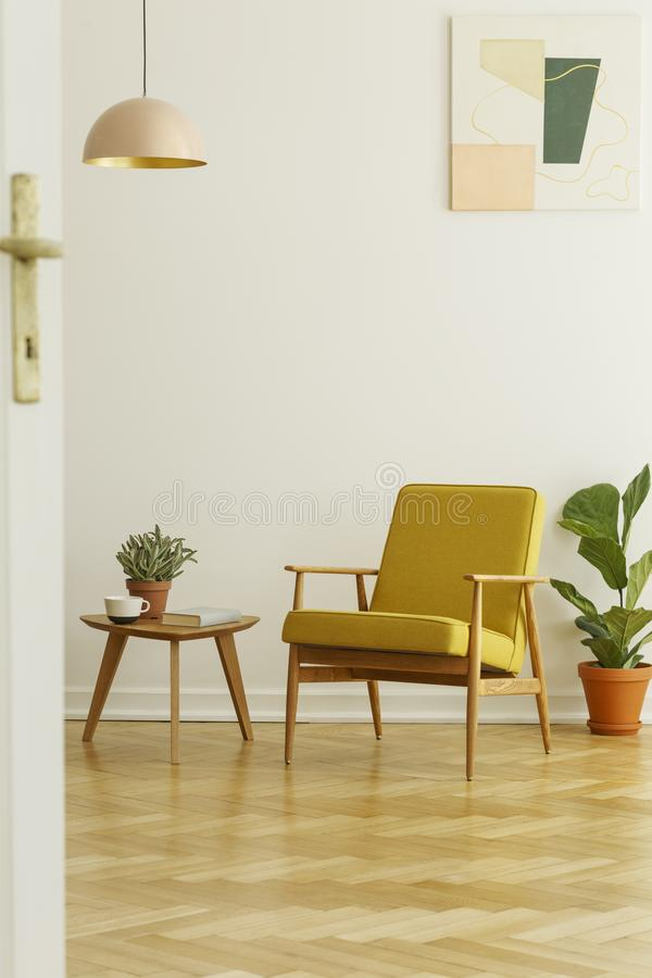 Yellow armchair and coffee table with a cup and plant on a herringbone parquet in a living room interior. Real photo stock image