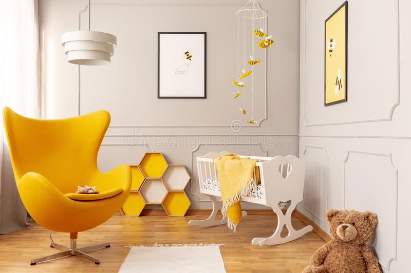 Yellow armchair, honeycombs and crib in a toddler room interior. Real photo stock images