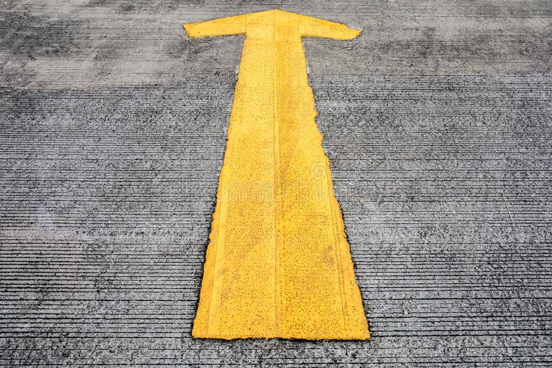Yellow arrow on the concrete ground of street or road of car parking. royalty free stock photo