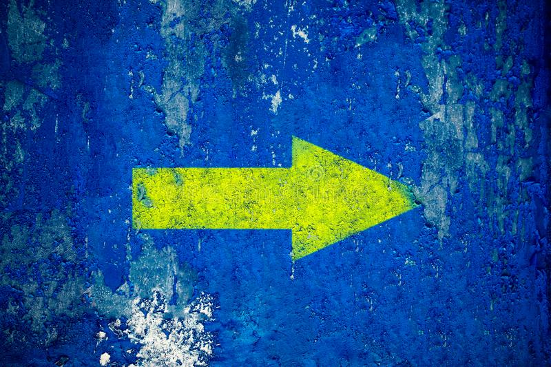 Yellow arrow painted on old grunge and weathered blue wall texture background stock photo
