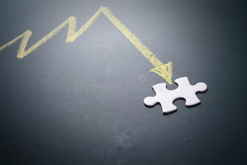 Graph drawing pointing down to jigsae puzzle royalty free stock photo