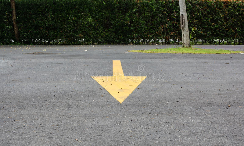 Yellow arrow sign from backward to front on parking lot stock photography