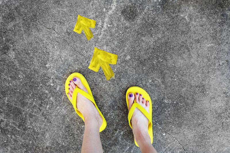 Yellow Arrows Direction. Woman's Sandals Feet with Violet Nail Pedicure on Cement Background royalty free stock images