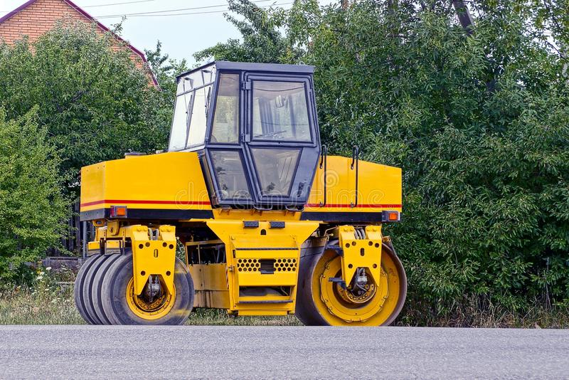 Yellow asphalt paver standing by the roadside near trees. Industrial vehicle for laying asphalt on the roadside near green trees royalty free stock photography