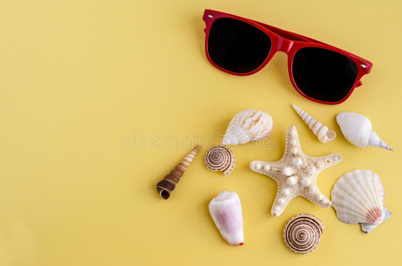Yellow background with copy space and shell border, red summer vacation sunglasses stock photos