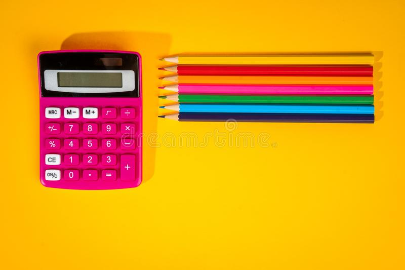 Yellow background with a crayons, calculator, ruler and felt-tip pens. Yellow school background with a crayons, calculator, ruler and felt-tip pens royalty free stock photos