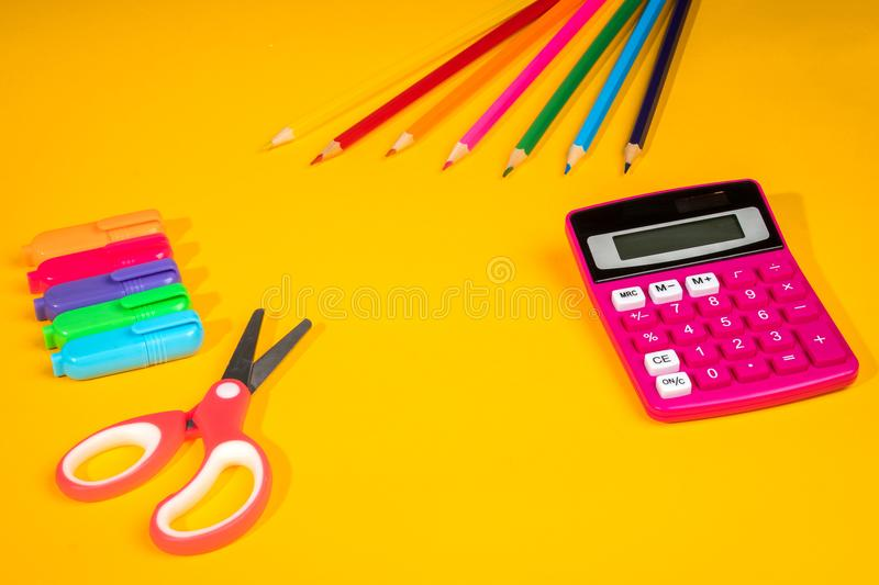 Yellow background with a crayons, calculator, ruler and felt-tip pens. Yellow school background with a crayons, calculator, ruler and felt-tip pens royalty free stock image