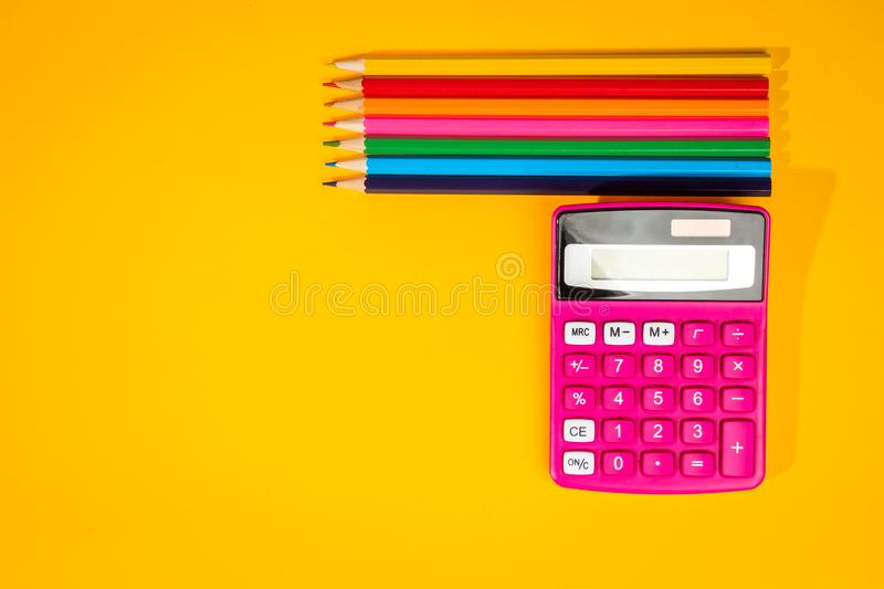 Yellow background with a crayons, calculator, ruler and felt-tip pens. Yellow school background with a crayons, calculator, ruler and felt-tip pens stock photography