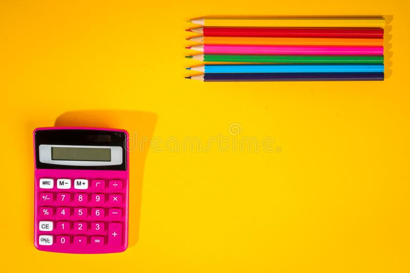 Yellow background with a crayons, calculator, ruler and felt-tip pens. Yellow school background with a crayons, calculator, ruler and felt-tip pens stock photo