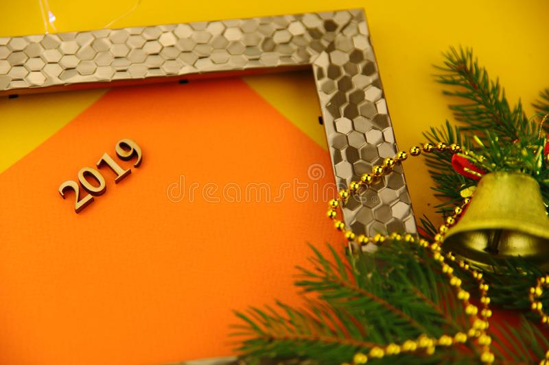 On a yellow background with a gold photo frame and a branch of spruce with toys is a card with numbers 2019. Abstract Christmas background. On a yellow royalty free stock photos