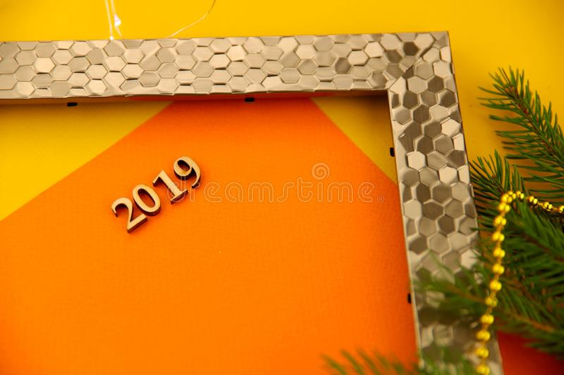 On a yellow background with a gold photo frame and a branch of spruce with toys is a card with numbers 2019. Abstract Christmas background. On a yellow royalty free stock images