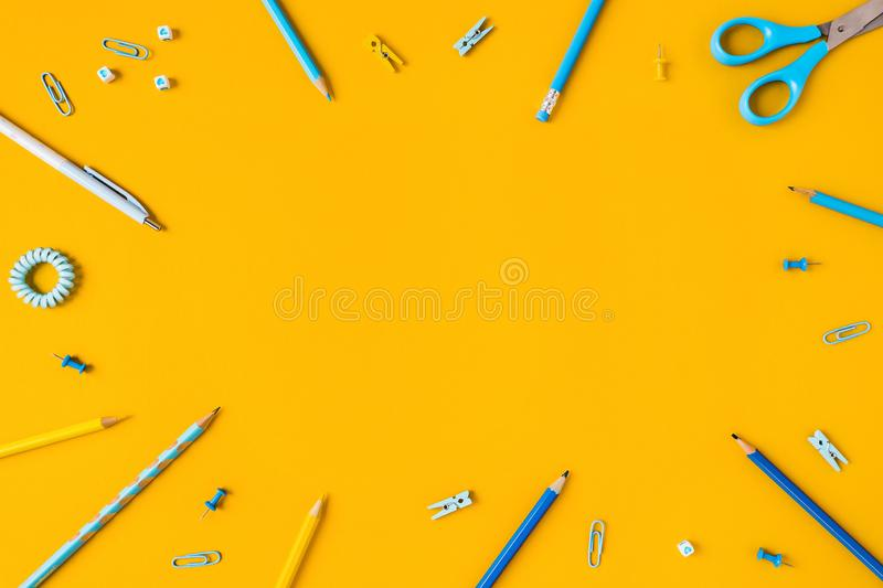 Yellow background with pens and pencils for school advertising. stock images