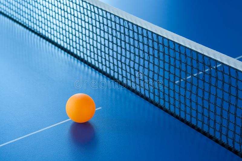 Yellow ball for table tennis lies on a blue table royalty free stock image