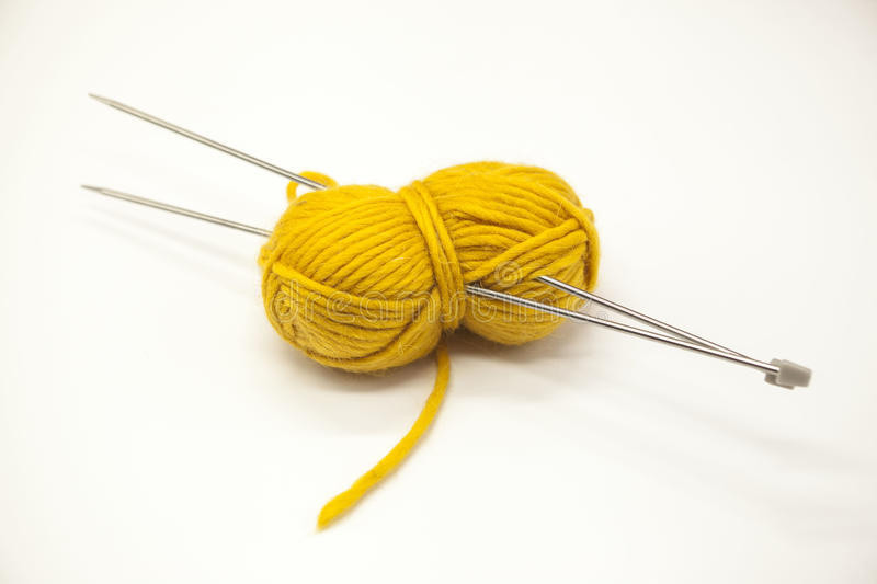Yellow ball of yarn for knitting with spokes on a white background. Yellow ball of yarn for knitting with spokes on a white background royalty free stock photos