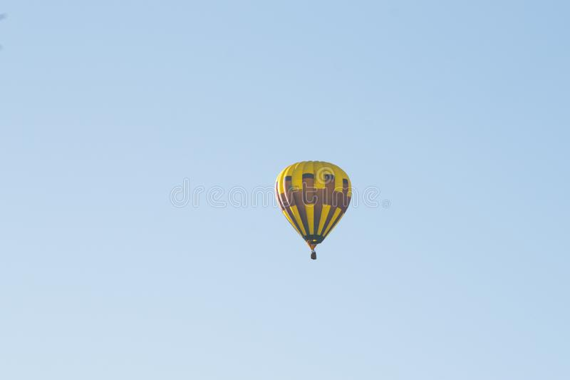 Yellow balloon against a blue sky. Aerostat. People in the basket. Fun. Summer entertainment. Romantic adventures. Red balloon against a blue cloudy sky. Sun stock images