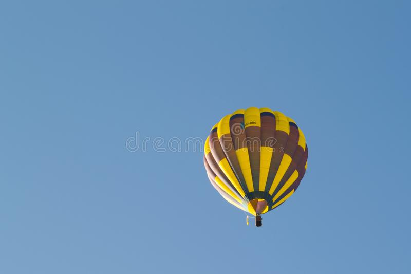 Yellow balloon against a blue sky. Aerostat. People in the basket. Fun. Summer entertainment. Romantic adventures. Red balloon against a blue cloudy sky. Sun royalty free stock photos