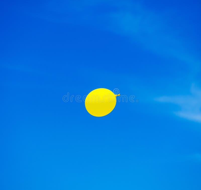 yellow balloon flying into sunny blue sky stock photos