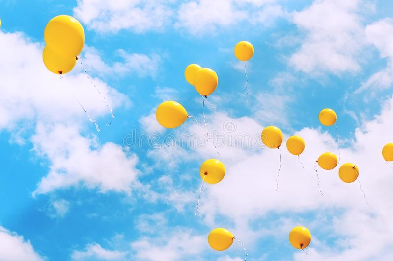 Balloons in the blue sky flying away. Toned, soft focused. royalty free stock photo