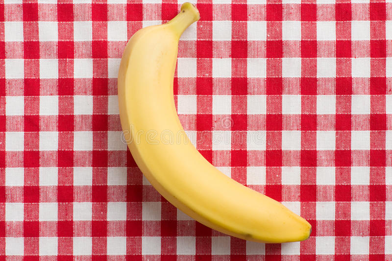 Yellow Banana On Checkered Tablecloth Stock Photos