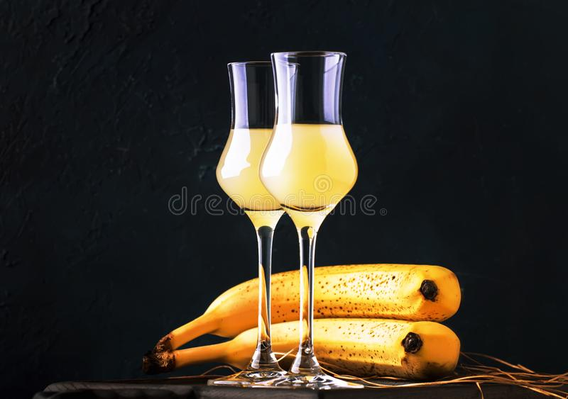 Yellow Banana liqueur in shot glasses and fresh ripe bananas on the table on dark blue background stock images