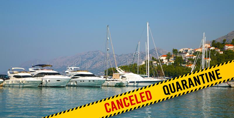 Canceled of travel, concept, Mediterranean city. Yellow barrier tape with the word Canceled and Quarantine. Marina with yachts in a Mediterranean city stock photo