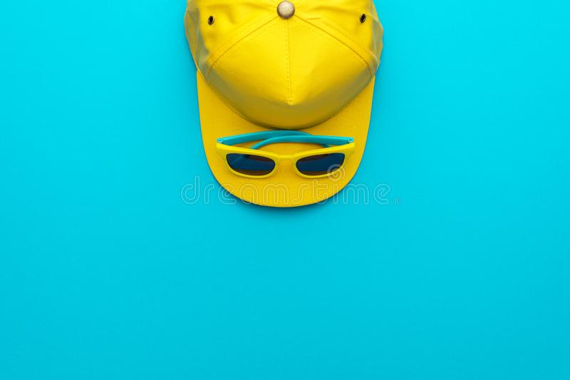 Yellow baseball cap and sunglasses on blue background with copy space stock images