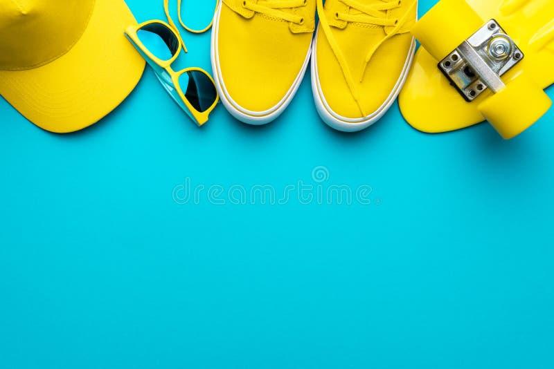 Yellow baseball cap, sunglasses, sneakers, mini cruiser board on blue background stock photo