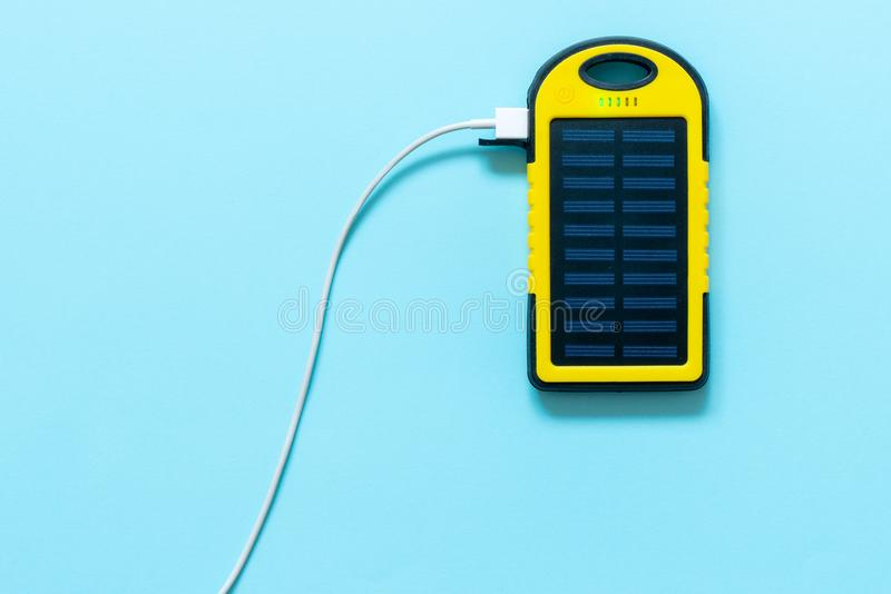 Yellow Battery solar power device on a blue background. royalty free stock photo