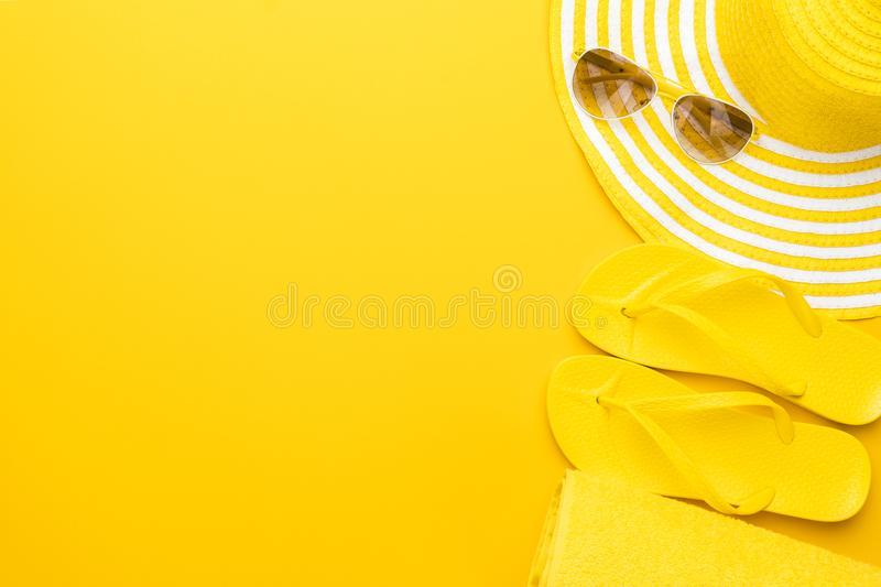 Beach accessories on the yellow background - sunglasses, towel. flip-flops and striped hat. summer is coming concept.  royalty free stock image