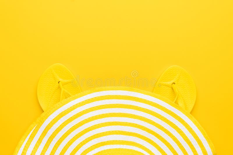 Beach flip-flops and hat on the yellow background with copy space. summer concept stock photo