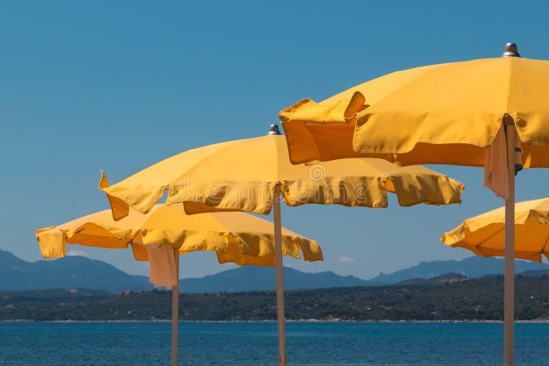 Yellow Beach Umbrellas in Line Near Shoreline. Hills and Sea in background stock photo