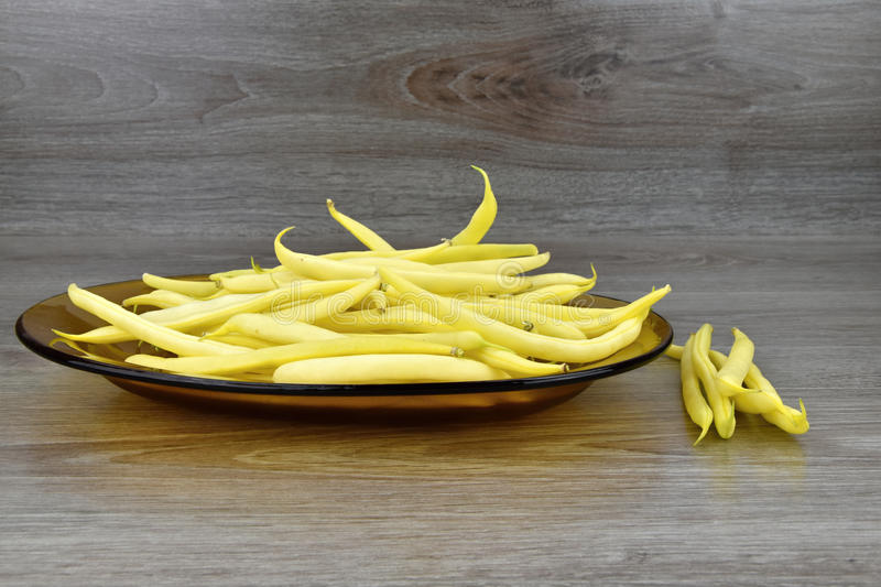 Yellow bean pods on the glass plate, background wood. Yellow bean pods royalty free stock photo