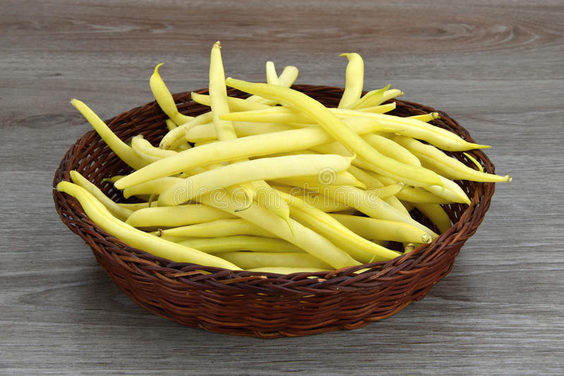Yellow bean pods in wicker bowl, white background. Yellow bean pods royalty free stock image