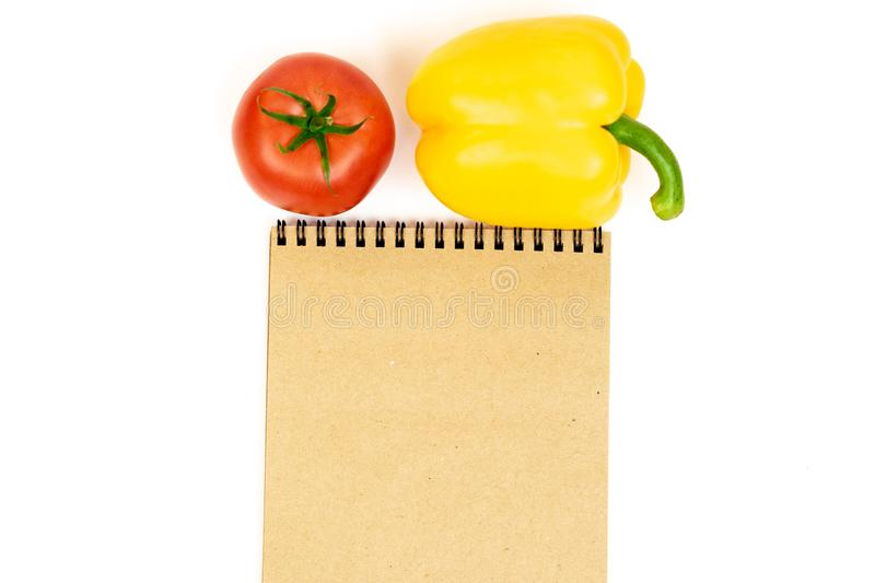 Yellow bell pepper with tomatoes isolated on white background near Notepad. Composition of yellow pepper and red tomato on a white stock image
