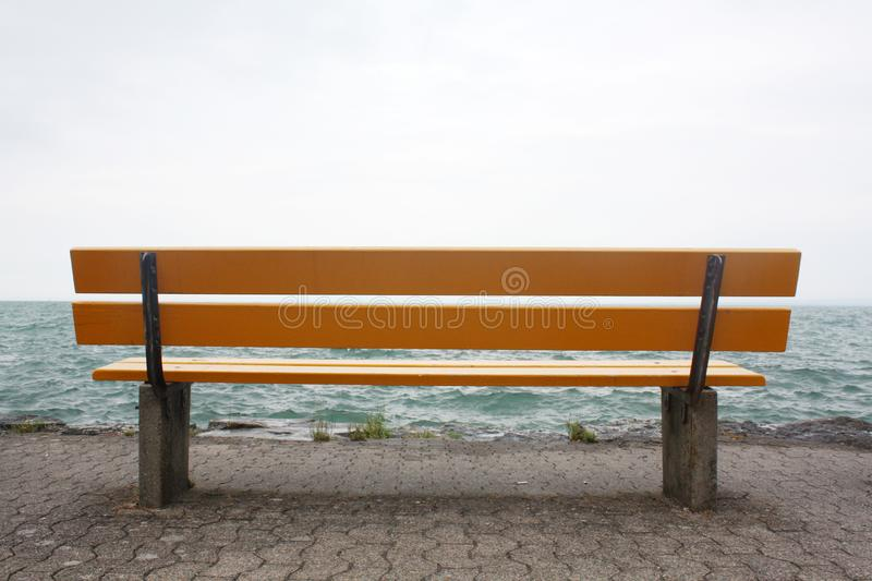 Yellow bench on the lake in Switzerland. royalty free stock photography