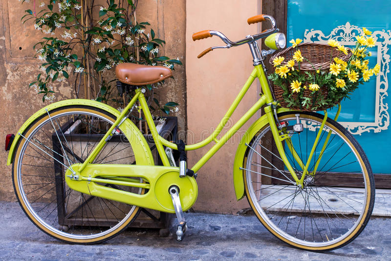 Yellow bicycle with basket of flowers royalty free stock photography