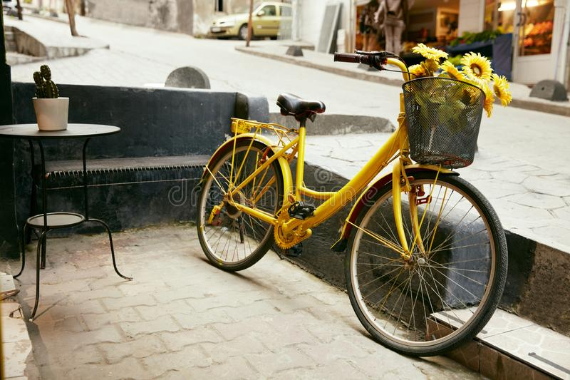 Yellow Bicycle With Basket Of Sunflowers At City Street royalty free stock images