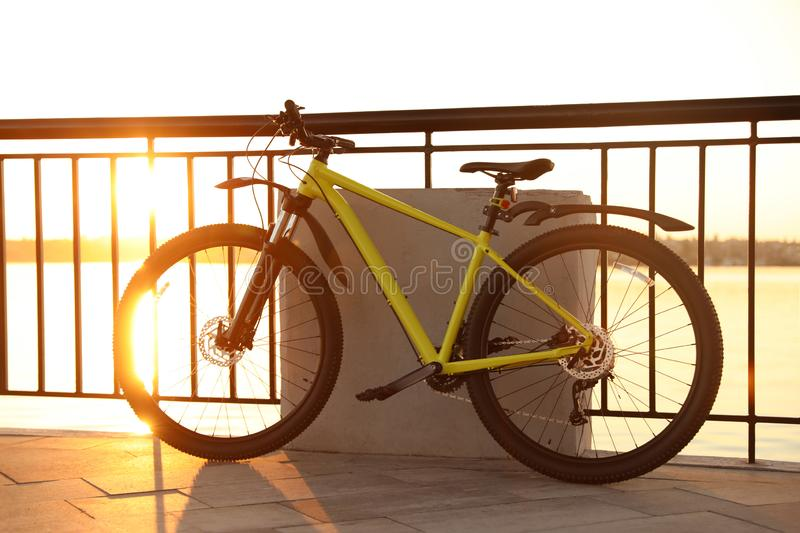 Yellow bicycle parked near  on city waterfront at sunset. Yellow bicycle parked near railing on city waterfront at sunset royalty free stock photography