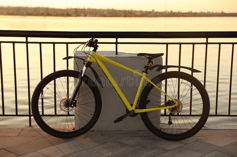 Yellow bicycle parked near  on city waterfront at sunset. Yellow bicycle parked near railing on city waterfront at sunset stock photo