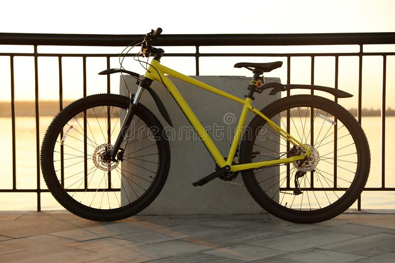 Yellow bicycle parked near railing on city waterfront. At sunset royalty free stock photography