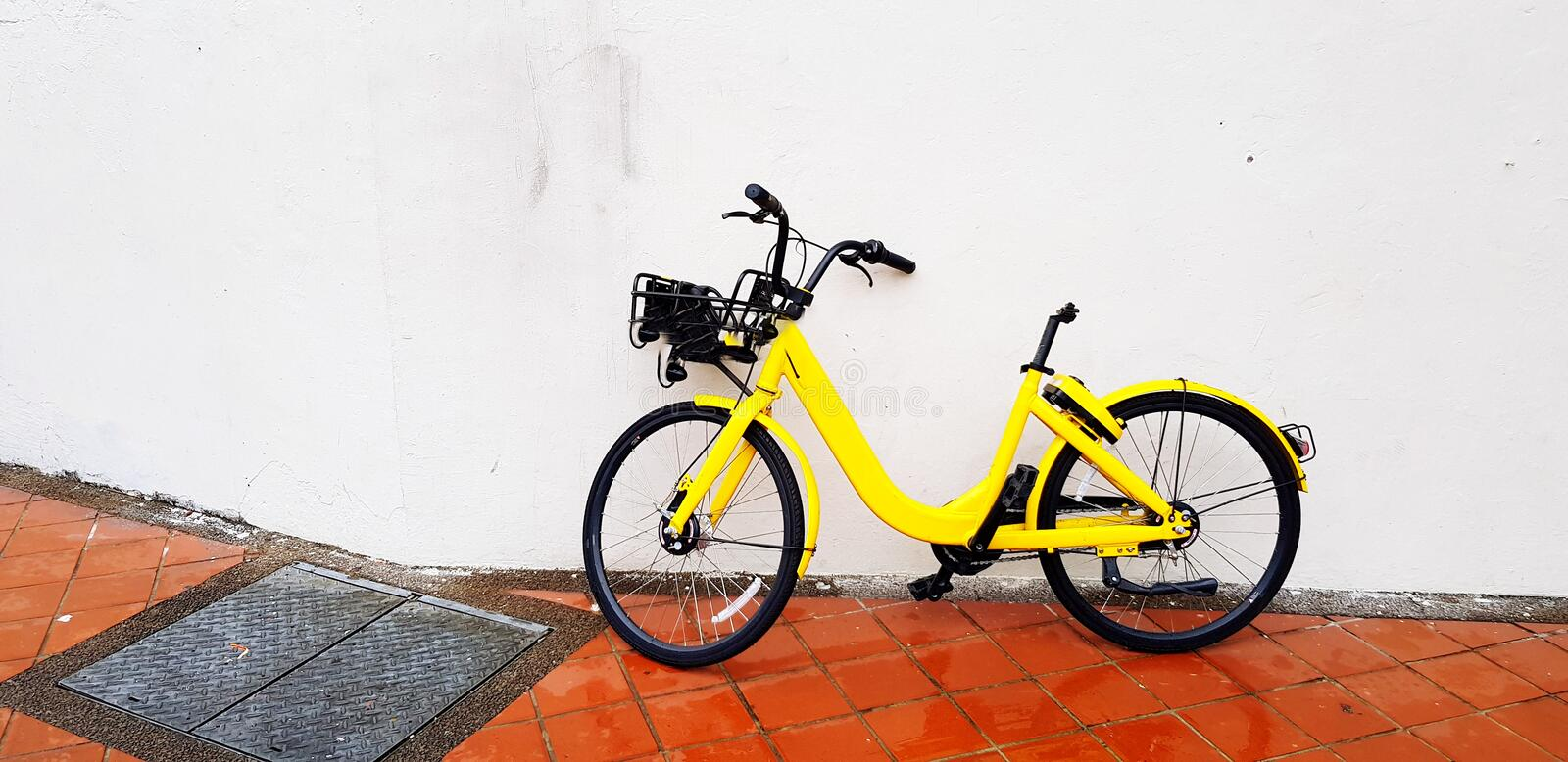 The yellow bicycle for rent park or lean on the white concrete wall royalty free stock image