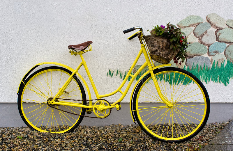 Yellow Bike. A yellow bike leaning on a white wall stock photography