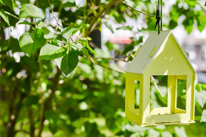 Yellow bird house hanging from the tree and surrounded by lush foliage stock images