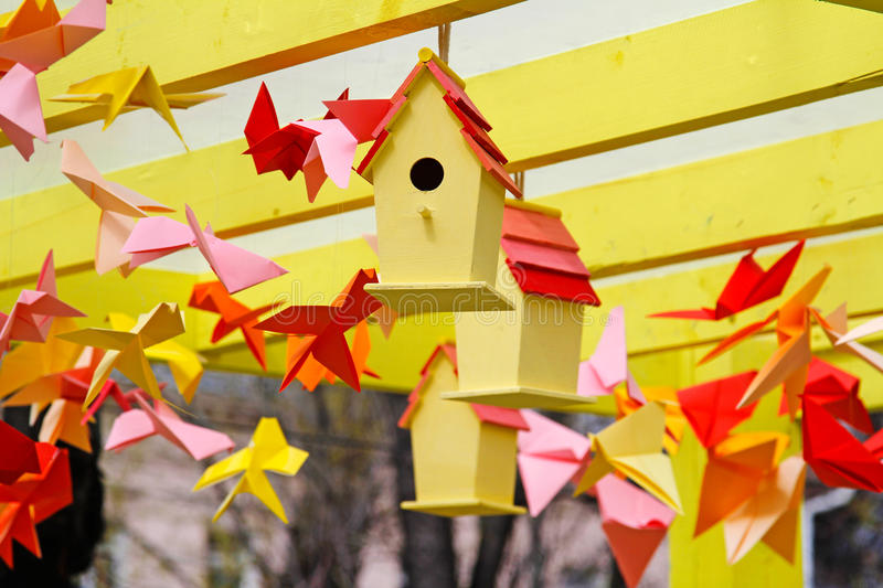 Download Yellow Birdhouses And Colorful Origami Birds Stock Photo