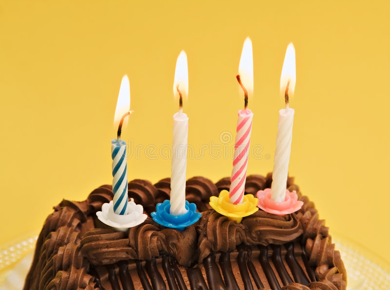 Yellow Birthday Cake. Chocolate birthday cake with candles against a yellow background stock images