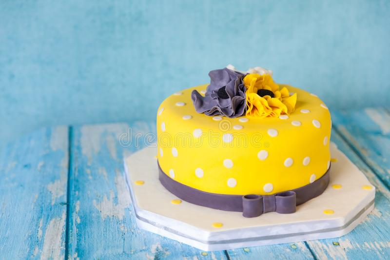 Yellow birthday cake with anemones. Yellow birthday cake with white, grey and yellow anemones flowers on blue wooden background stock image